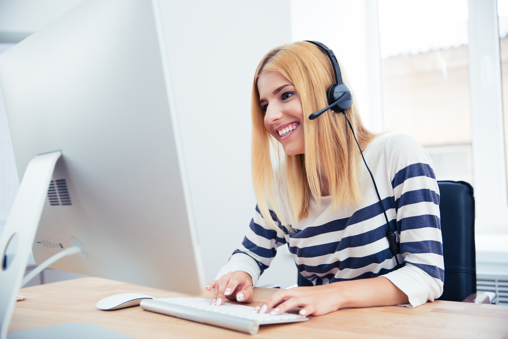 Cheerful young female operator with headset using desktop computer in office