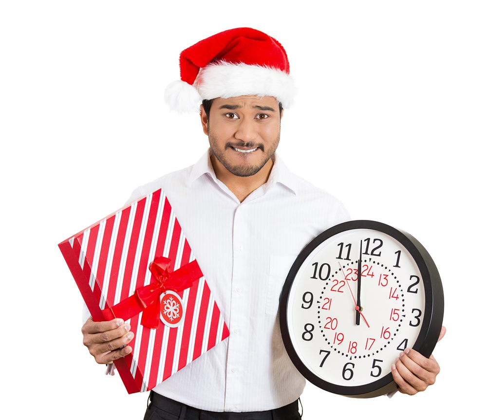 Closeup portrait of worried young man wearing red santa claus hat, holding clock and gift in hands, isolated on white background. Negative emotion facial expression. Last minute christmas shopping